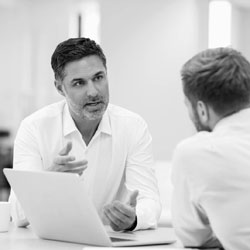 black and white photo showing two men discussing business next to laptop